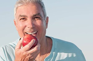 Older man eating an apple